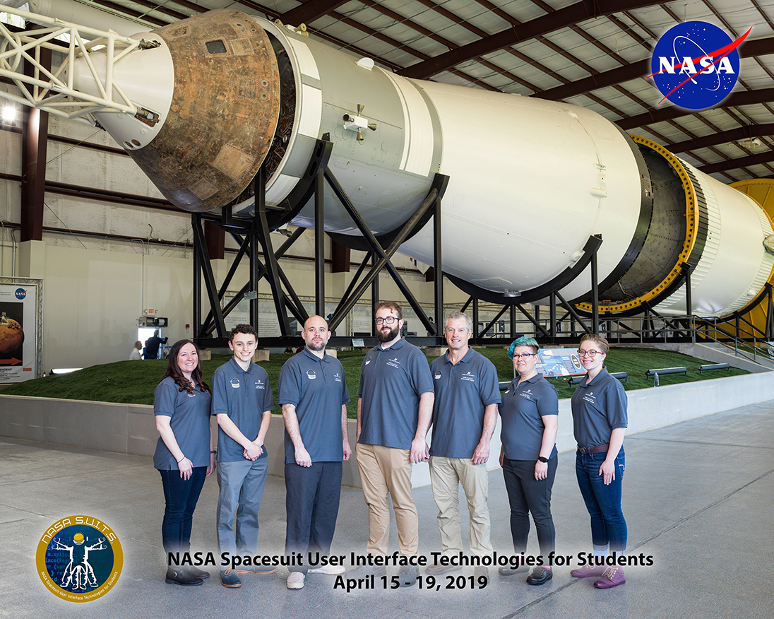 Boise State University NASA SUITS Onsite Team Photo in front of the Saturn IV Rocket in Rocket Park. Left to Right: Dr. Karen Doty, Dean Cohen, Daniel Lambert, Taylor Campbell, Ret. NASA Astronaut Steve Swanson, Liz Altmiller, and Brenna Leonard.